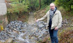 Radny Tomasz Piszczek wskazuje wykonane w ostatnim czasie kamienne umocnienie brzegów na Potoku Karniowskim przy jednym z budynków w Psarach (Fot.: Robert Siwek).